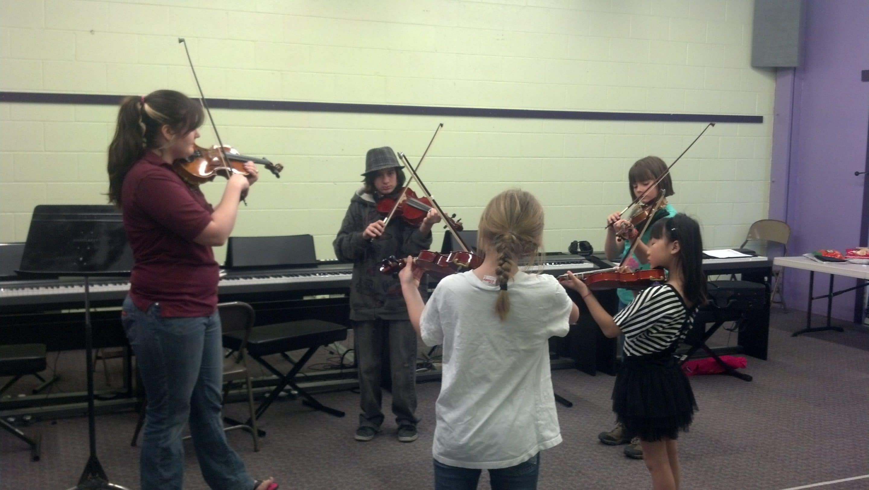 Sarah teaching a group of children violin