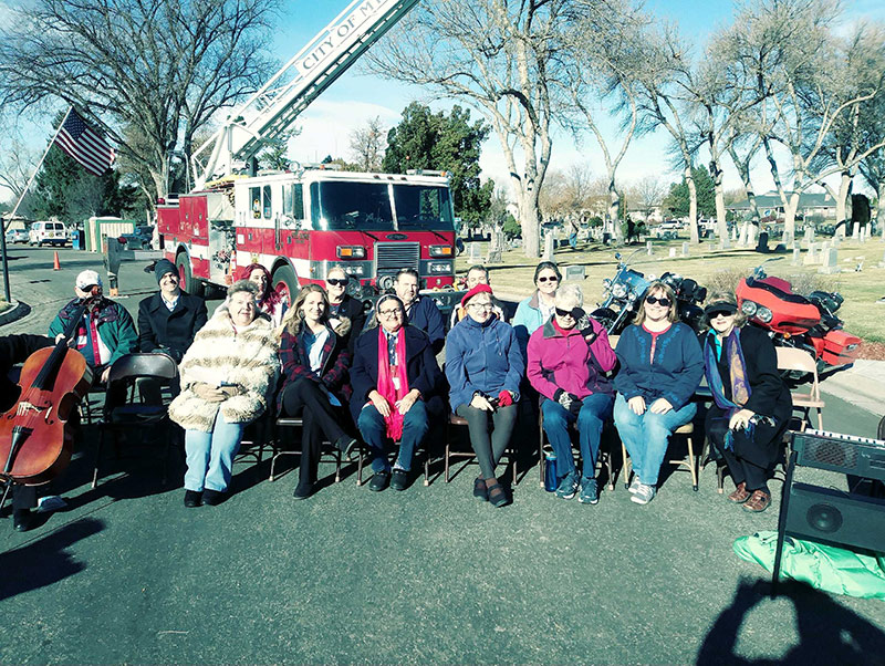 Community choir sitting in front of a fire truck at a park