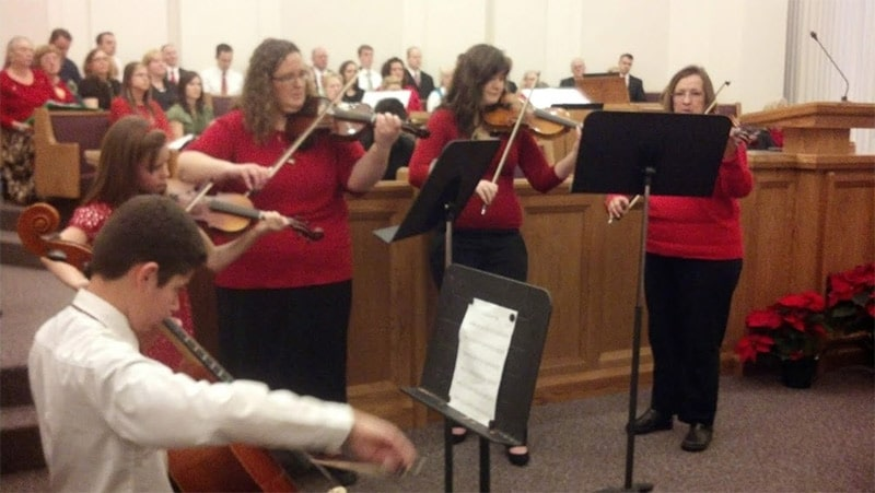 String chamber orchestra playing in front of a choir